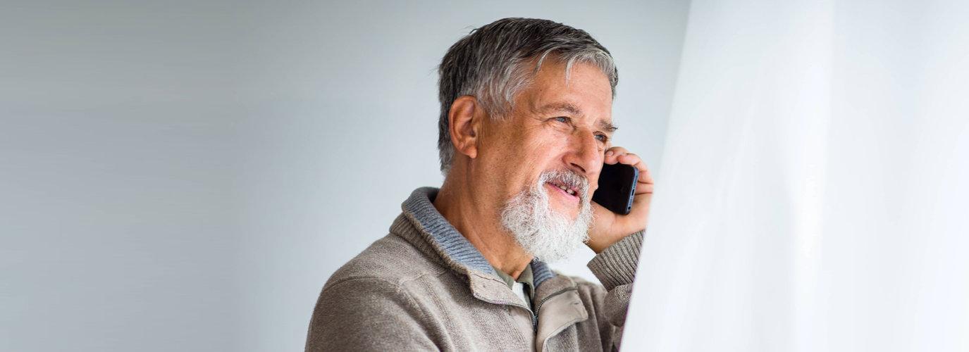 senior man answering the phone smiling
